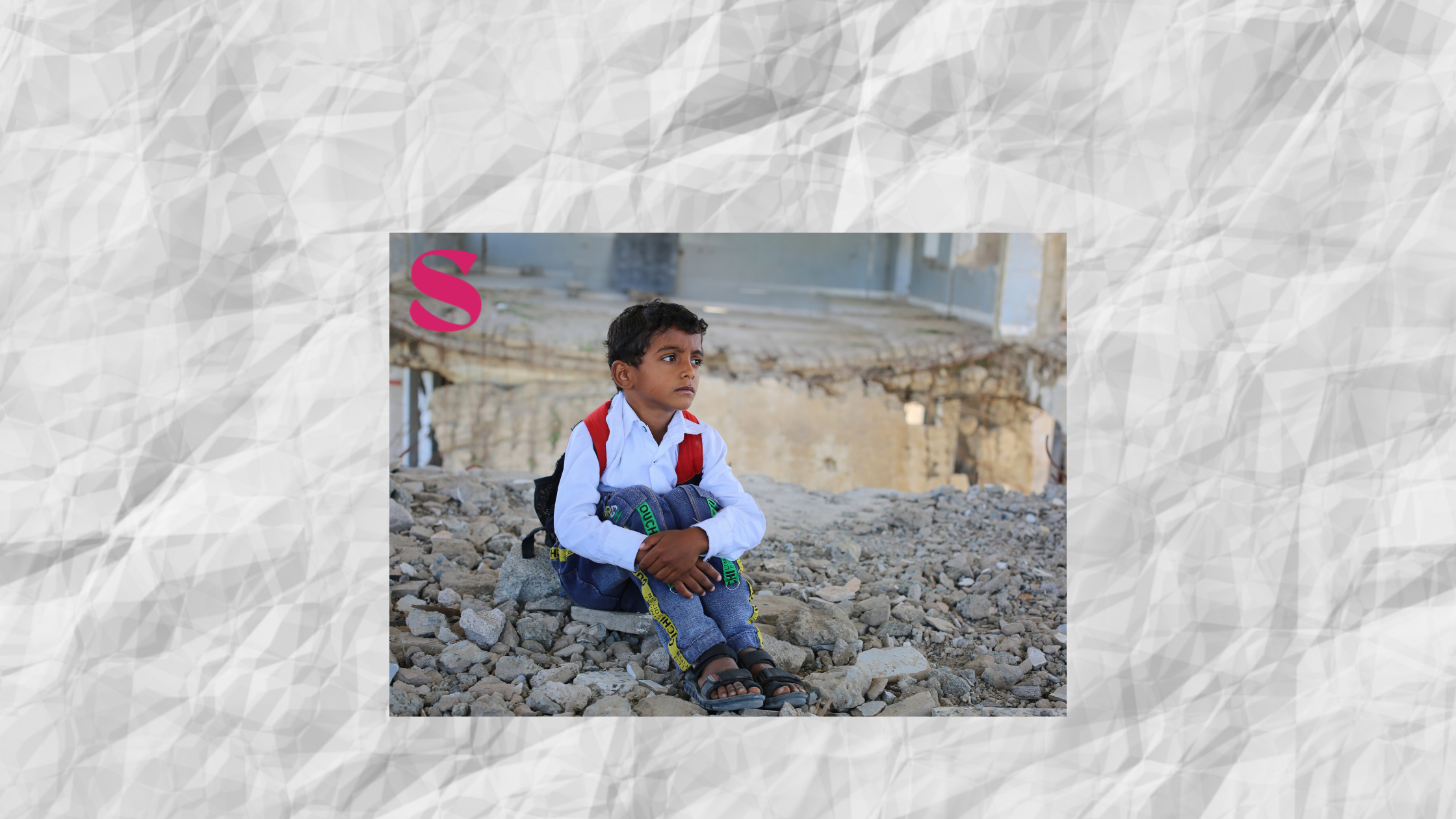Young Yemen boy sitting on a pile of rubble